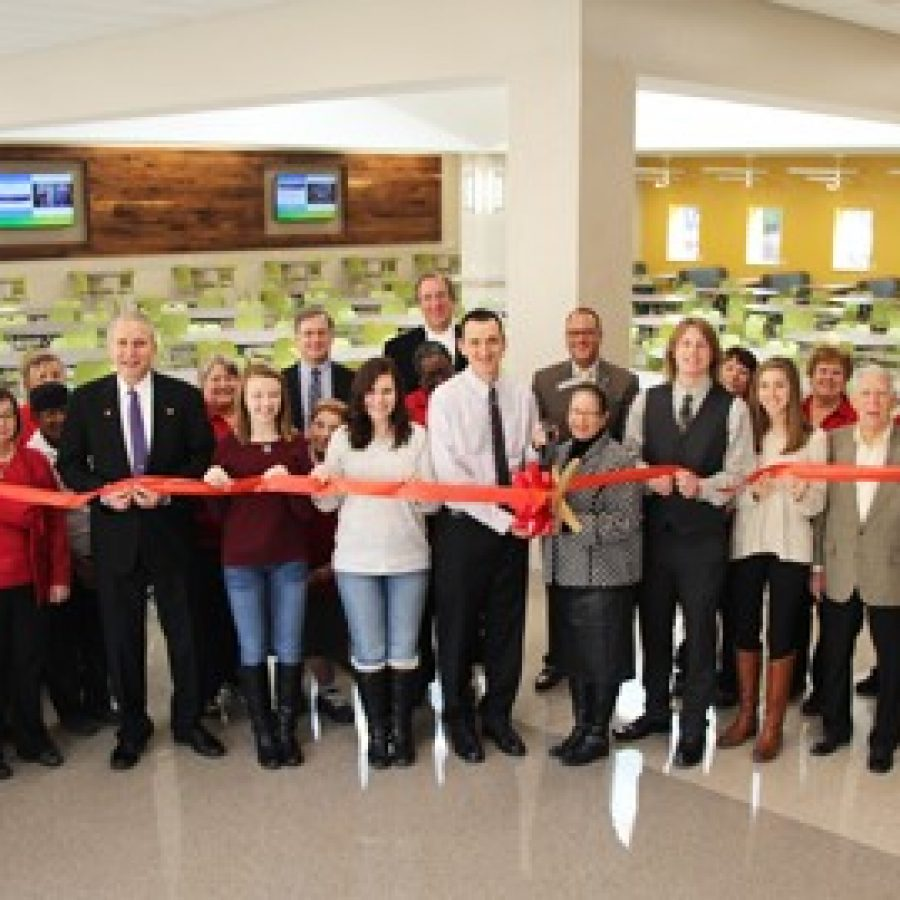 Lindbergh High School Principal Eric Cochran and Chartwells Director of Dining Services Gloria Holliday, center with scissors, celebrate the grand opening of the Lindbergh High cafeteria expansion on Friday. They are joined by students, administrators, Board of Education members and Chartwells staff.