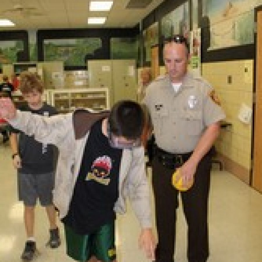 Truman Middle School School Resource Officer Jeff Kriska uses special goggles to show students how drinking can impair motor functions.