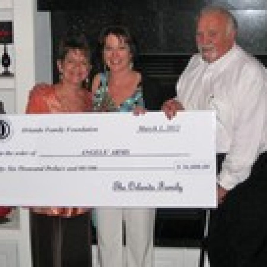 Jan Orlando, left, and Sam Orlando, right, present a check for \$36,000 to Bess Wilfong, executive director of Angels' Arms.
