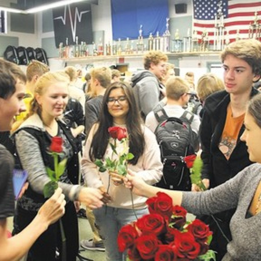 Lindbergh High Assistant Marching Band Director Chelsea Silvermintz, right, presents red roses to band members last week, following an announcement that they have been selected to perform in the 2018 Tournament of Roses Parade.