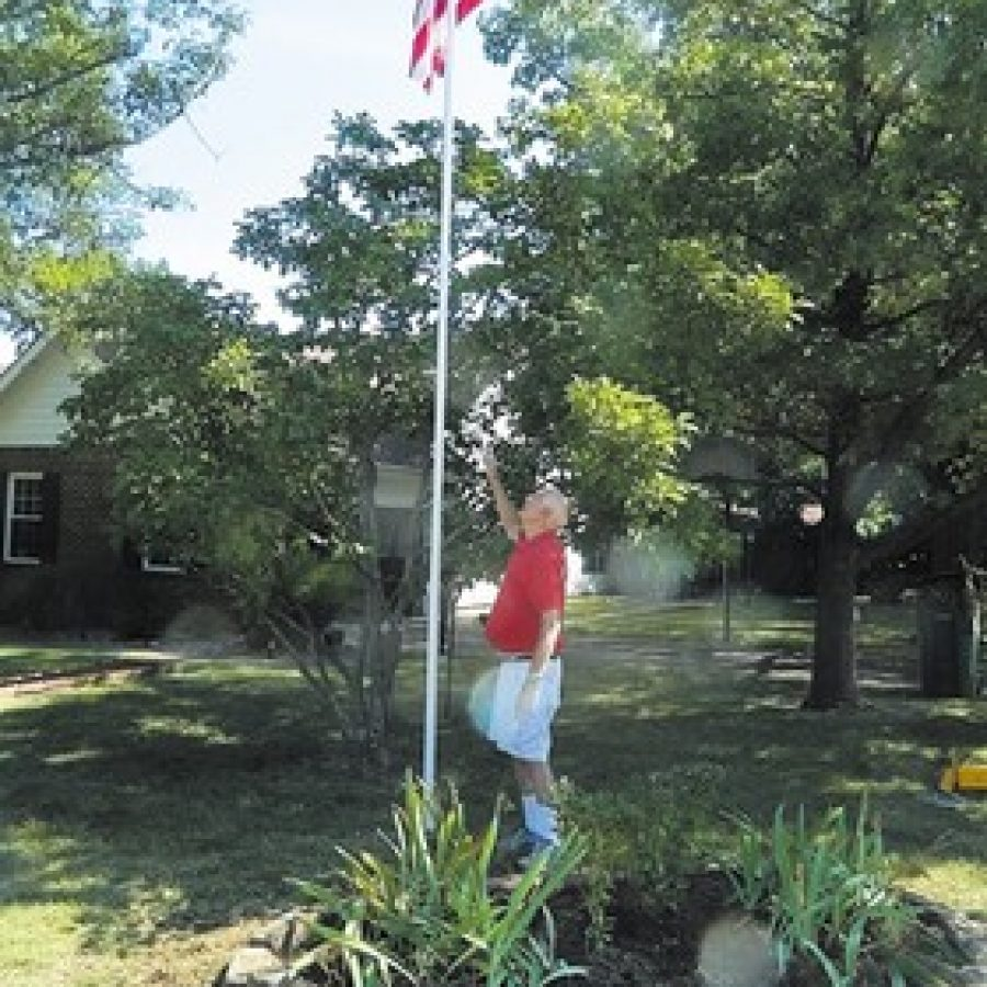 Crestwood Army veteran Gene Mentel salutes the flag flying on his flagpole that was restored by his neighbors.