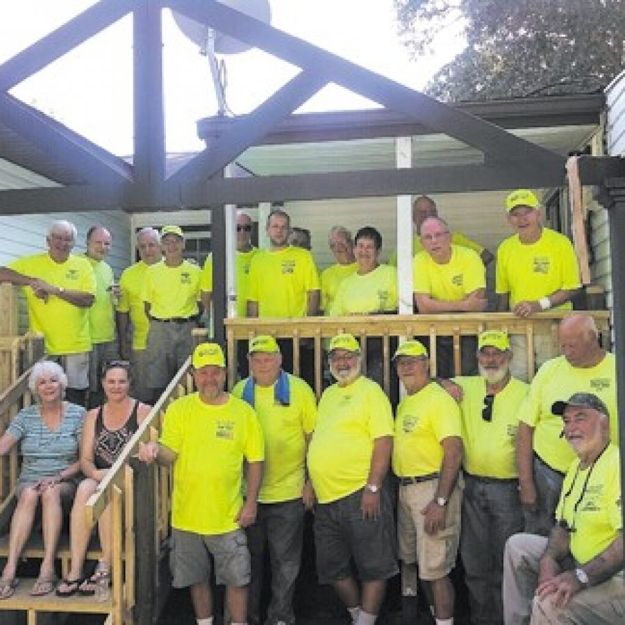 Members of the St. Louis Sluggers from the Queen of All Saints Catholic Church are pictured on the newly constructed back porch of the home they worked on near Shoal Creek.