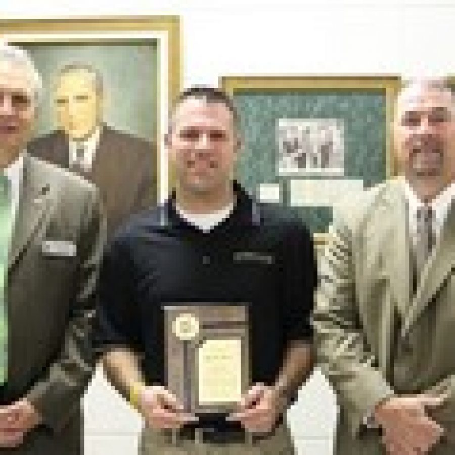 Superintendent Jim Simpson, left, and Assistant Superintendent of Personnel Rick Francis, right, present the 2012-2013 Lindbergh Teacher of the Year Award to Brian Wyss, middle-school director of bands.