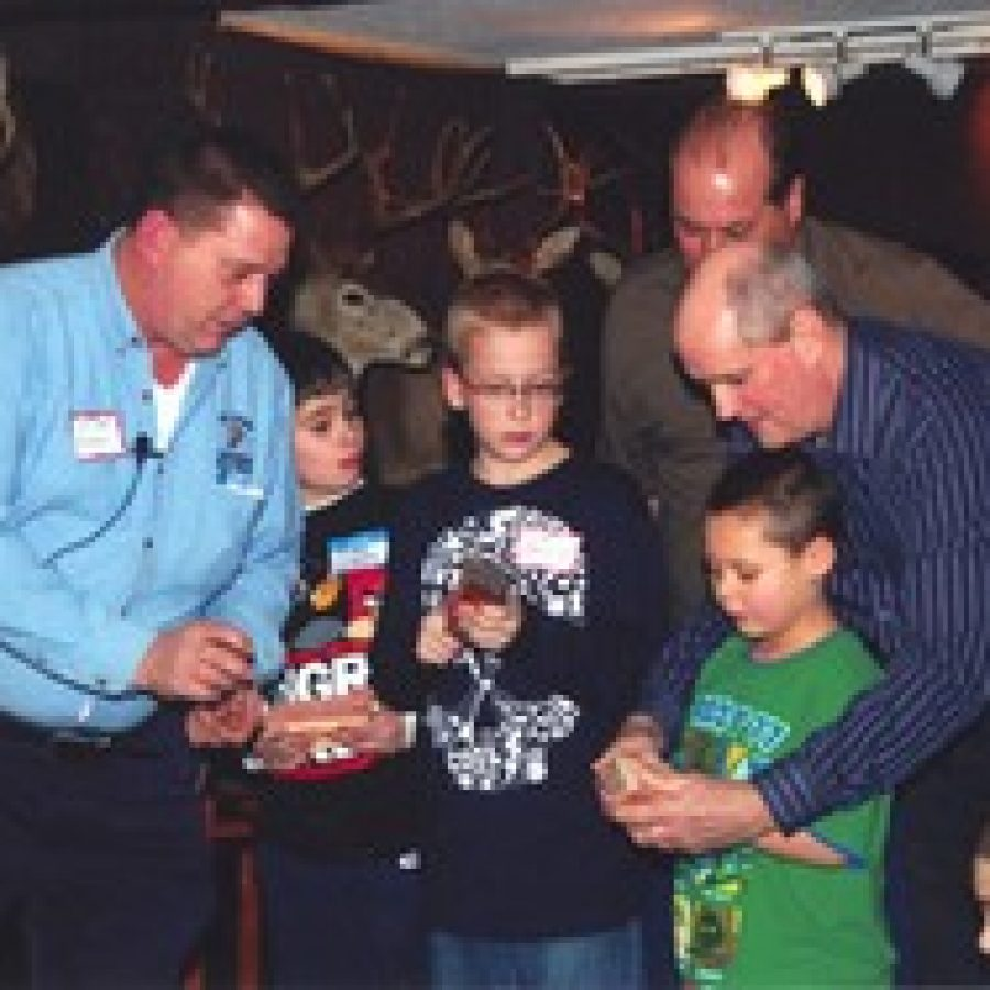 Mitch Norris, left, of the St. Louis Chapter World Turkey Federation, gives turkey-calling lessons to youngsters at the First Baptist Church of Oakville's fourth annual Pioneer Harvest Dinner.
