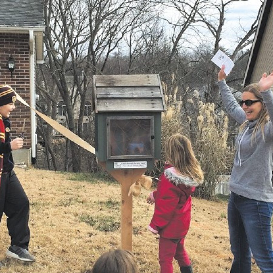 Jenny Bess, right, celebrates the official opening of Oakville's new Little Free Library with her children, from left, Sawyer, 10, and Lottie, 6.