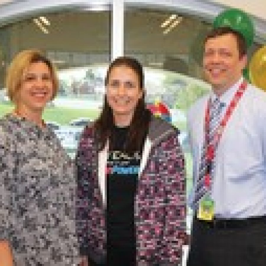 Sappington Elementary Principal Craig Hamby, right, and Administrative Intern Angie Moehlmann, left, congratulate physical education teacher Mary Driemeyer on being named Lindbergh's 2014 Teacher of the Year.