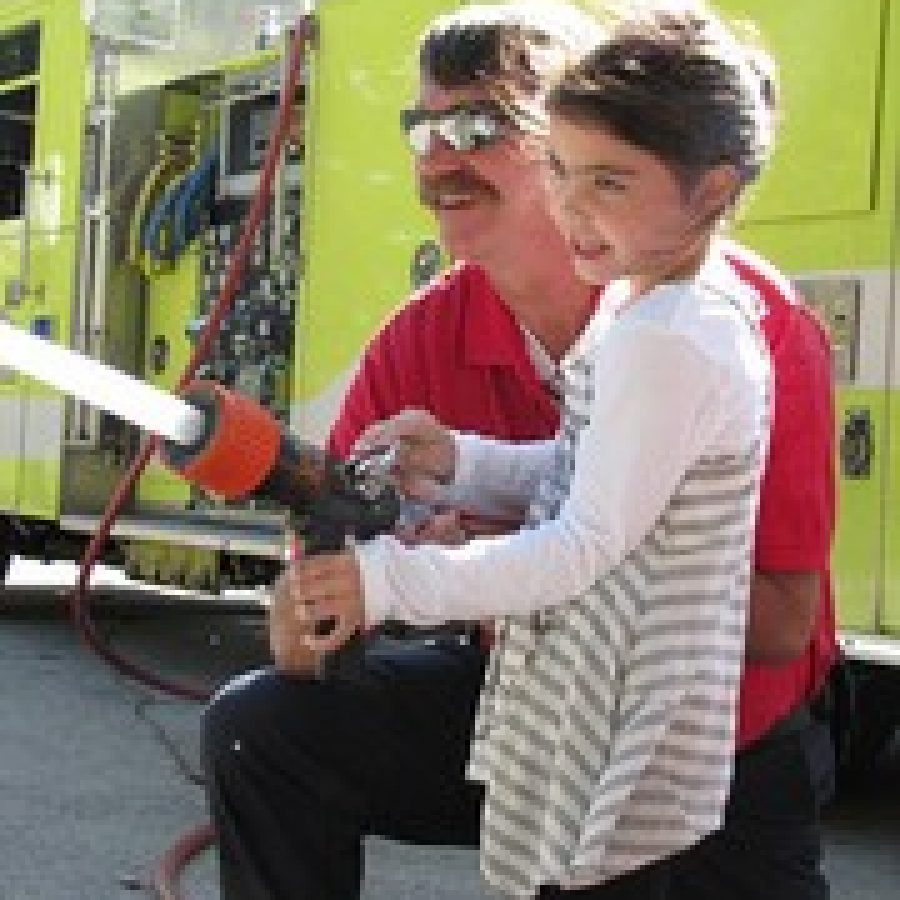 Long Elementary School kindergarten student Rosie Grebe takes her turn spraying a fire hose during National Fire Prevention Week. The Crestwood Fire Department visited Long and Crestwood elementary schools to talk with students about fire safety.