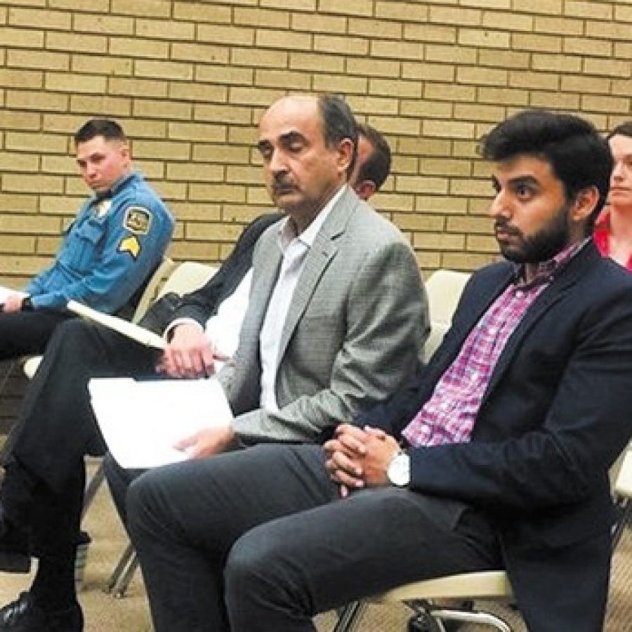 Sunset Hills Econo Lodge owner Shaiq Amir, center, is shown with his son Saiad Amir, right, at the Oct. 25 Board of Aldermen public hearing. Also pictured is police Sgt. Jeff Senior, left. Photo by Gloria Lloyd.
