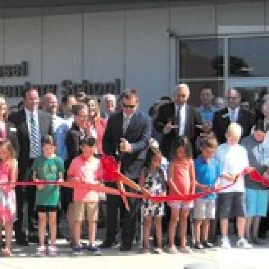 Lindbergh Schools Board of Education members, administrators, teachers and staff gathered last week along with former school board members, state and local elected officials, community leaders and members of the Dressel family to celebrate the opening of the district's 650-student Dressel Elementary School, as Dressel students cut the ribbon for the new state-of-the art school on the direction of Superintendent Jim Simpson, arms extended. Mike Anthony photo.