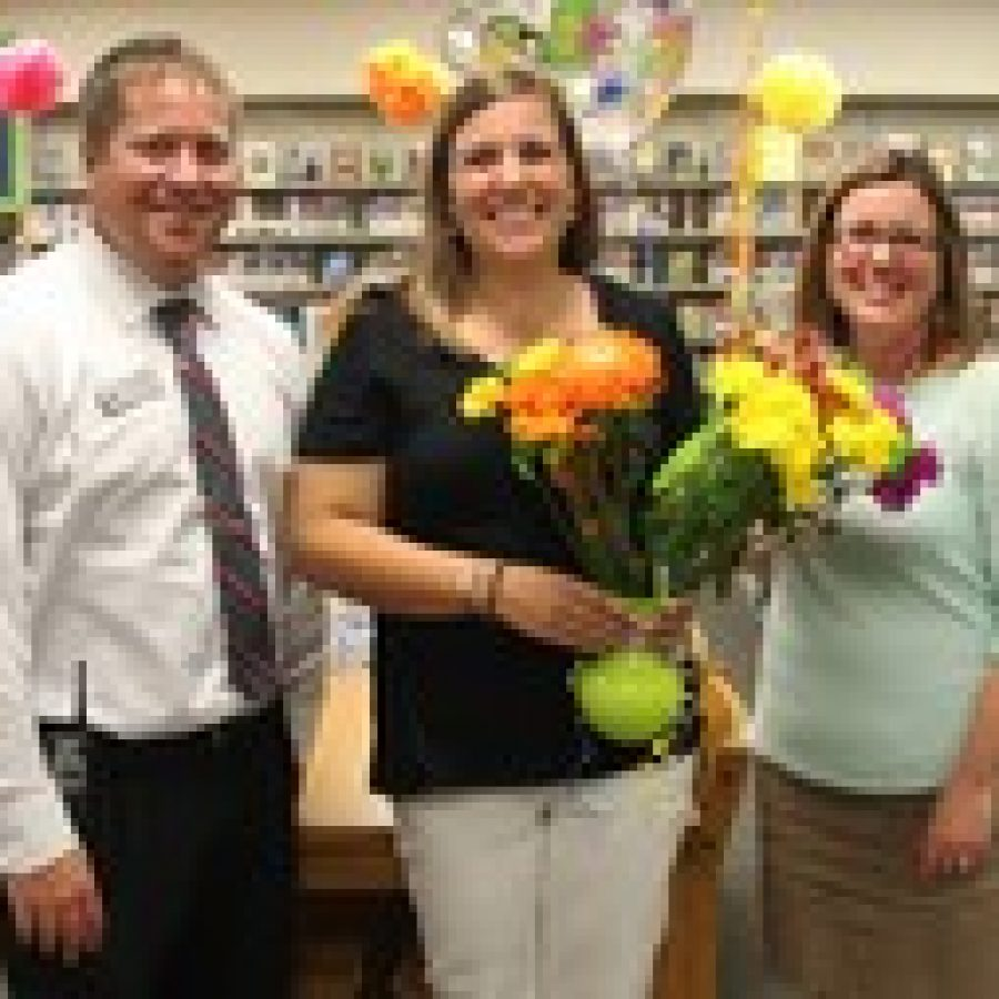 Truman Middle School science teacher Melissa Nussbaum, center, is congratulated by Principal Tara Sparks and Assistant Principal Mike Straatmann during a surprise announcement.