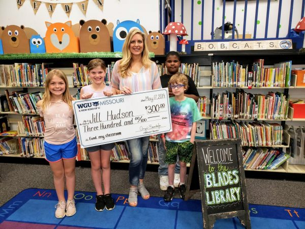 Students from Mrs. Rygelski's third-grade class at Blades Elementary School pose with Library Media Specialist Jill Hudson after she was presented in May 2019 with a check for $300 to fund her idea to bring pedal exercisers to the school library. Pictured from left to right are Ella Weber, Ashlyn Petlansky, Jill Hudson, Kaimen Matthis (back right) and Wesley Givens (front right).