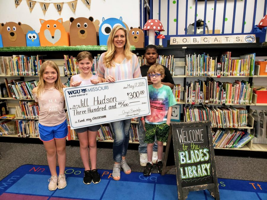 Students+from+Mrs.+Rygelski%E2%80%99s+third-grade+class+at+Blades+Elementary+School+pose+with+Library+Media+Specialist+Jill+Hudson+after+she+was+presented+in+May+2019+with+a+check+for+%24300+to+fund+her+idea+to+bring+pedal+exercisers+to+the+school+library.+Pictured+from+left+to+right+are+Ella+Weber%2C+Ashlyn+Petlansky%2C+Jill+Hudson%2C+Kaimen+Matthis+%28back+right%29+and+Wesley+Givens+%28front+right%29.