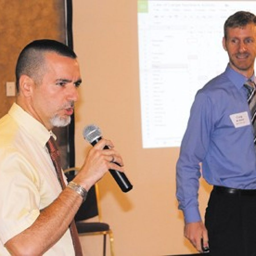 At the first 'Good Morning Mehlville-Oakville' event, Oakville High School teacher John Souris, left, explains how he and Mehlville High School teacher Corey Arbini, right, linked their classes with real-time technology for statistics lessons showing which school built the best paper airplanes.