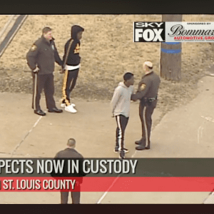 Two suspects, in handcuffs, are taken into custody by police on Union Road in south county Tuesday morning. Photo is taken from live coverage of the Skyfox helicopter from Fox 2.