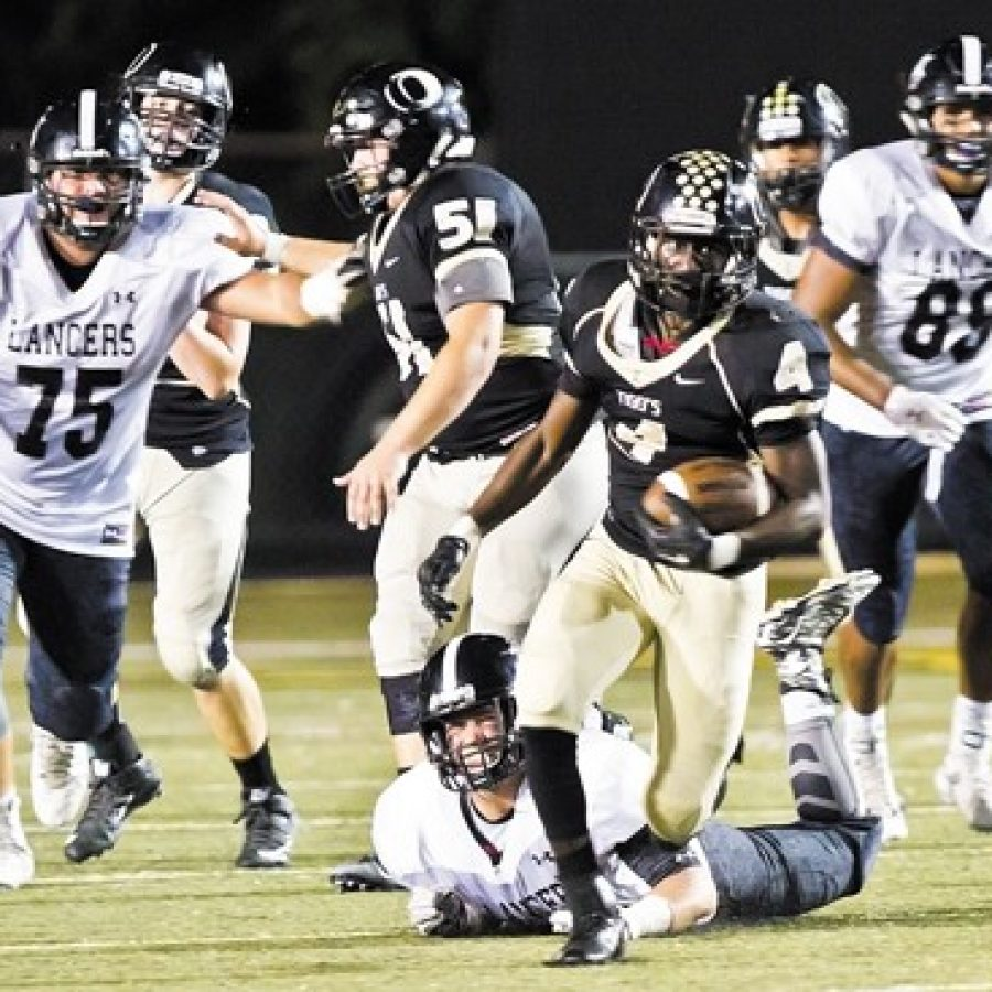The Oakville Senior High School football team fell 44-27 to the Lafayette Lancers Friday night in Oakville's Homecoming game. Above, Oakville High's Norvell Streeter, No. 4, is pursued by Lafayette's Chase Behrndt, No. 75, and Michael Farinella, No. 88.