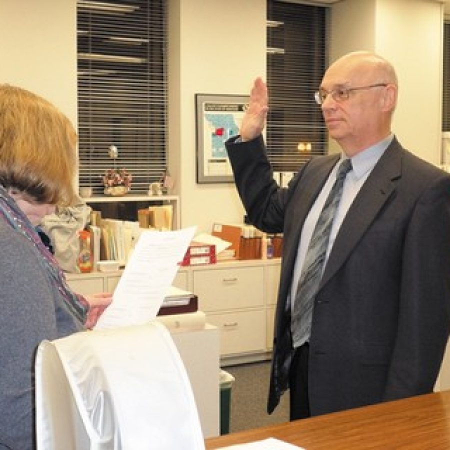 Deputy County Clerk Jeanette Hook administers the oath of office to Director of Revenue Greg Quinn last week. Quinn, a Republican who represented District 7 on the County Council for 23 years, was appointed to the post by County Executive Steve Stenger, D-Affton.