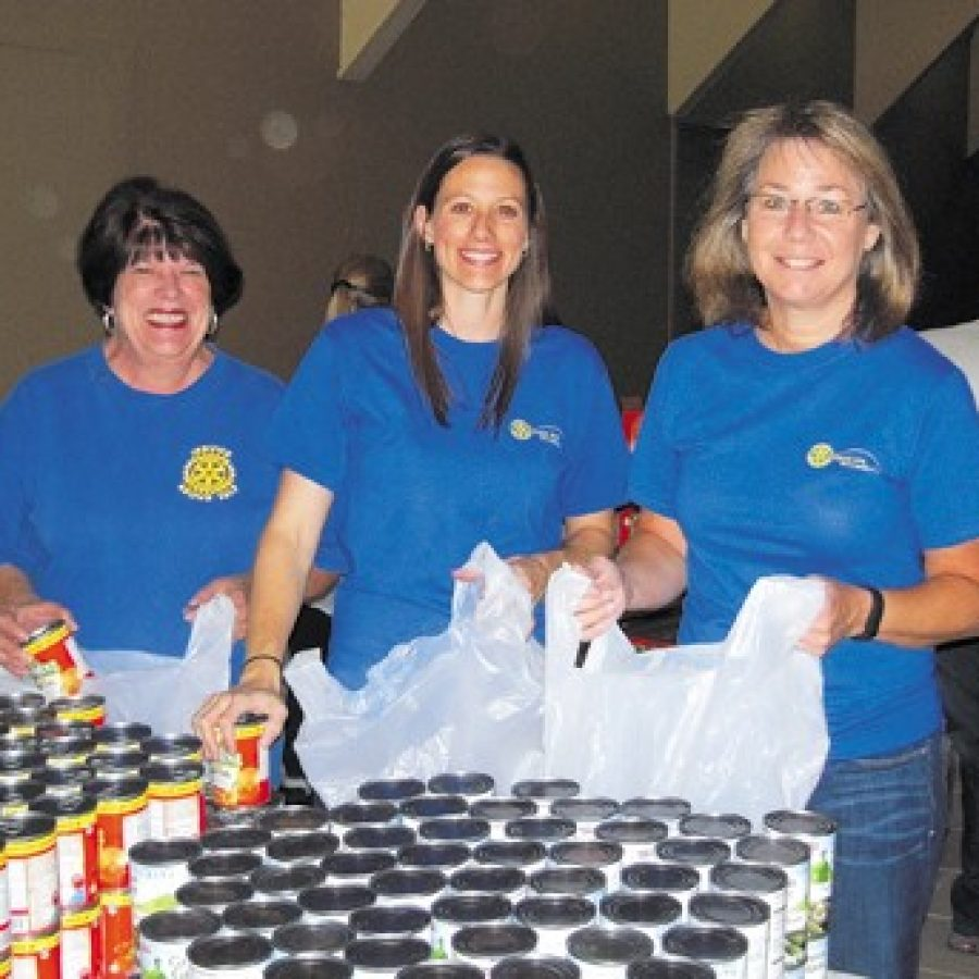 Rotary Club members, from left, Diana Lineberger, Chris Cipolla and Debby Schiavo pack food bags to be distributed to Lindbergh and Mehlville students.