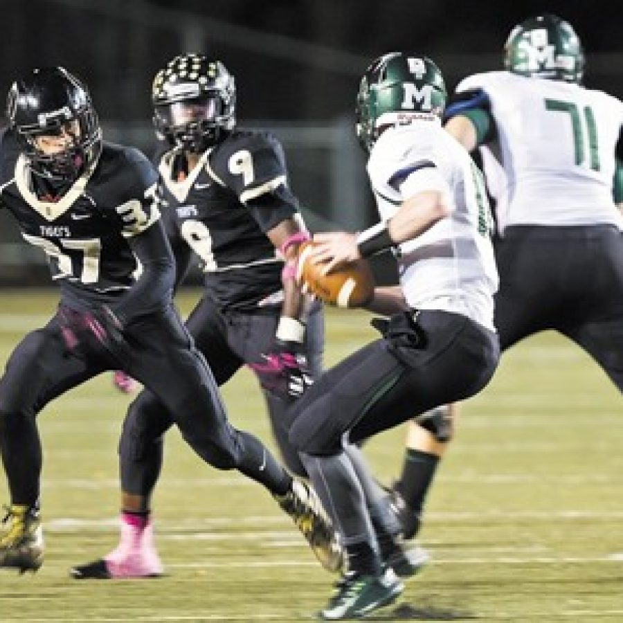 Oakville High's Christian Niehoff, No. 37, and Demetrius Harris, No. 9, pursue Mehlville's Brendan Mady, No. 10, in Friday night's game in which the Panthers edged the Tigers 17-14. Also pictured is Mehlville's Shane McGroaty, No. 71. Megan LeFaivre-Zimmerman photo