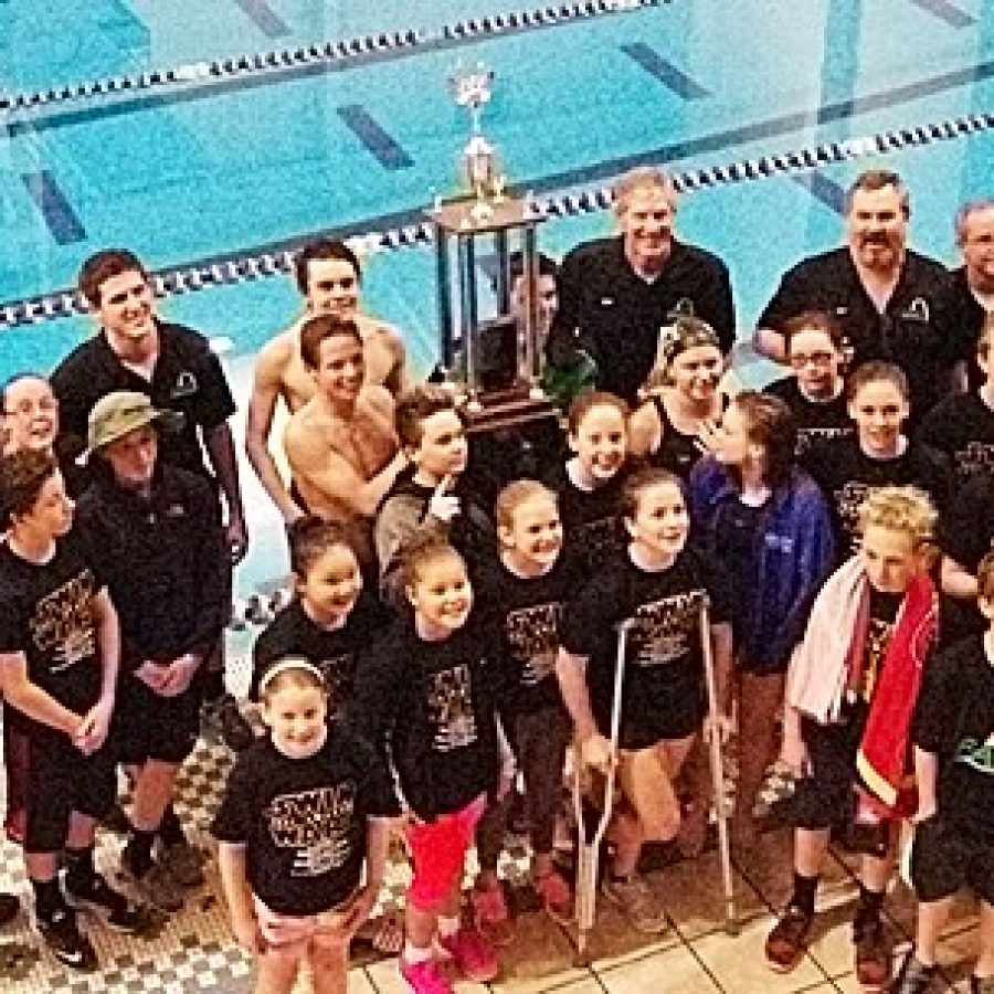 Members of Flyers Aquatic Swim Team are pictured with their trophy for winning the Ozark Swimming Division 1 Swim Meet championship for the second consecutive year.