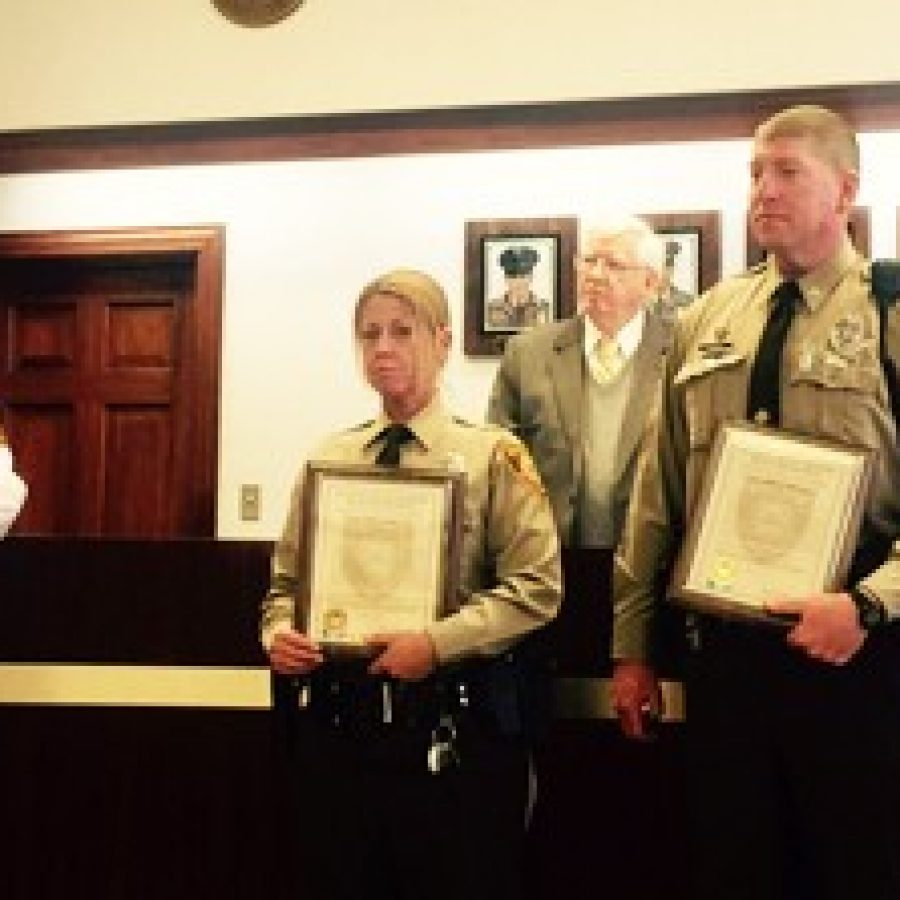 Capt. James Schneider, left, commander of the South County Precinct, explains the heroics of, front row from left, Officer Kelly Eller and Officer John Spicer, who were recently presented with the Lifesaving Award. Back row, from left, are police board members T.R. Carr and Chairman Roland Corvington.