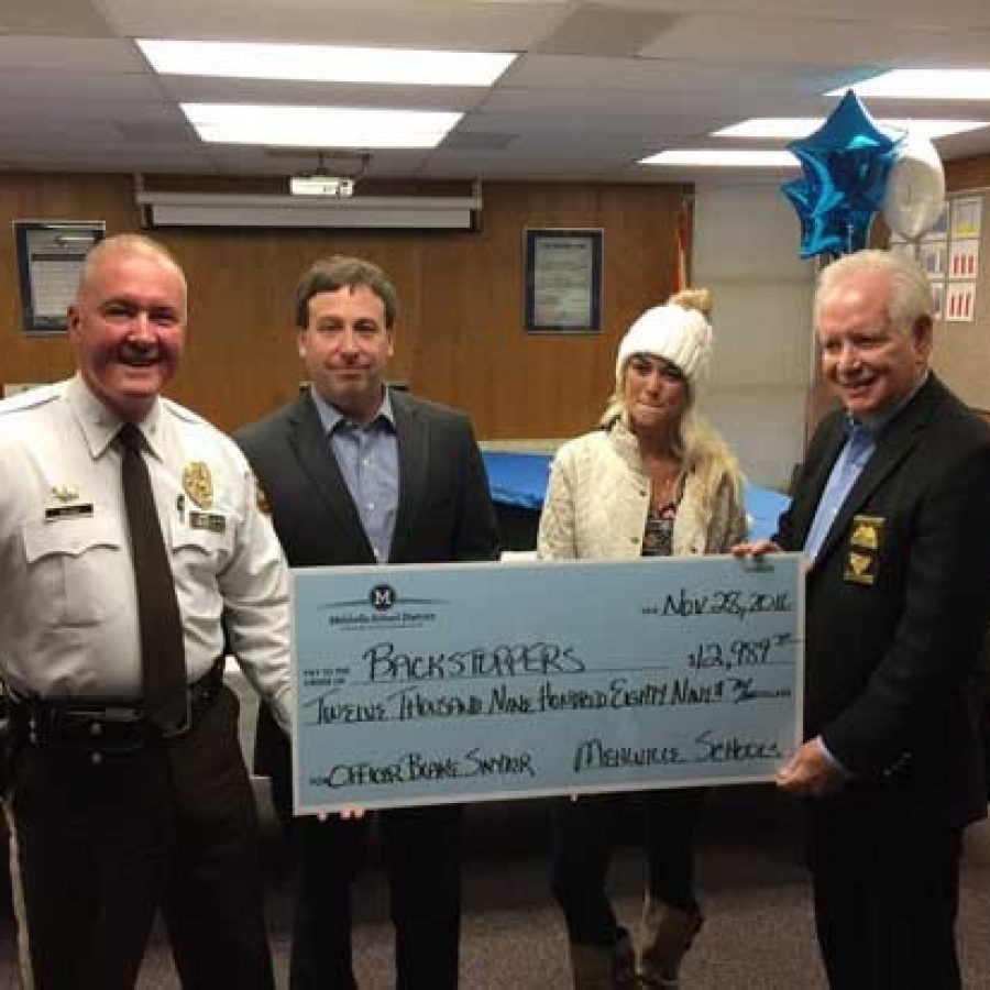 Elizabeth Snyder, second from right, accepts the Mehlville School District's BackStoppers donation with, from left, Chief Jon Belmar, County Executive Steve Stenger and former Chief Ron Battelle, now head of BackStoppers.