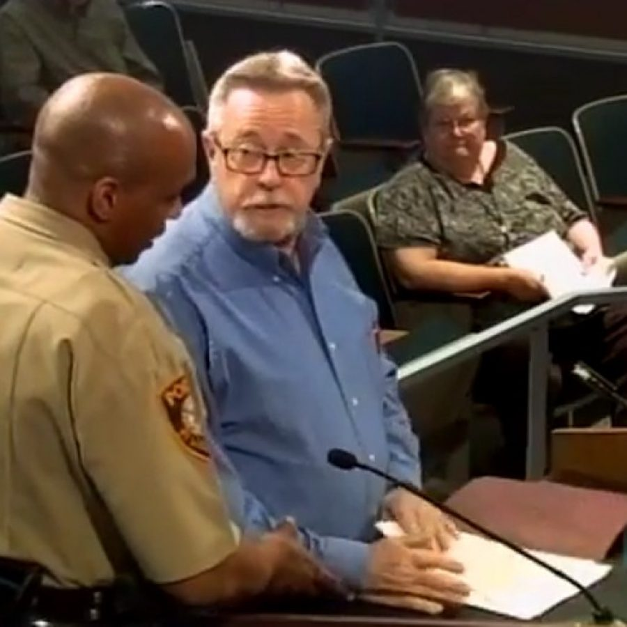 In this screenshot from the YouTube video of the March 22 County Council meeting, a county police officer, left, forces Oakville resident Jim Hamilton off the podium.