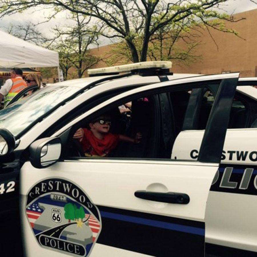 A young Crestwood resident tries out one of the city's police cars on display at the April 16 'Food Truck Party at the Plaza' celebration.
