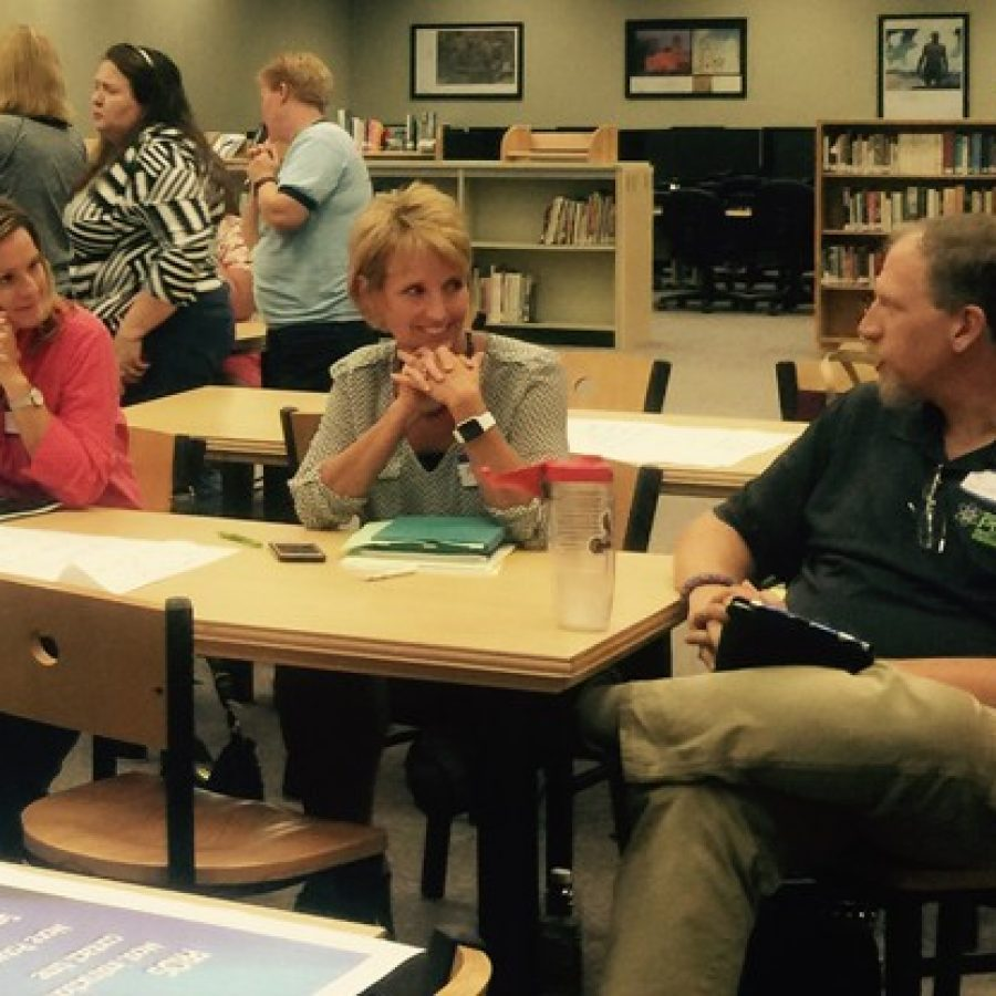 Scheduling Review Committee member and Oakville High School teacher Jim Kreyling, right, talks to fellow committee member Peggy Hassler, center, during last week's public meeting on block scheduling at OHS.