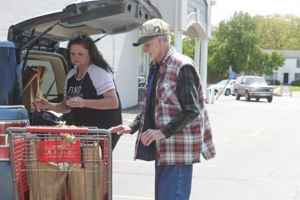 Caregiver Denise Phelps helps her 85-year-old uncle, William Speck, with groceries obtained from Feed My People in Lemay, Mo., on April 24