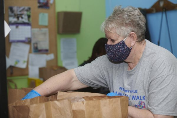 Feed My People volunteer Denise Huber follows COVID-19 safety precautions as she prepares and delivers grocery and personal care items provided by the nonprofit Feed My People at its facility in Lemay, Mo. It also operates a food pantry in High Ridge, Mo.