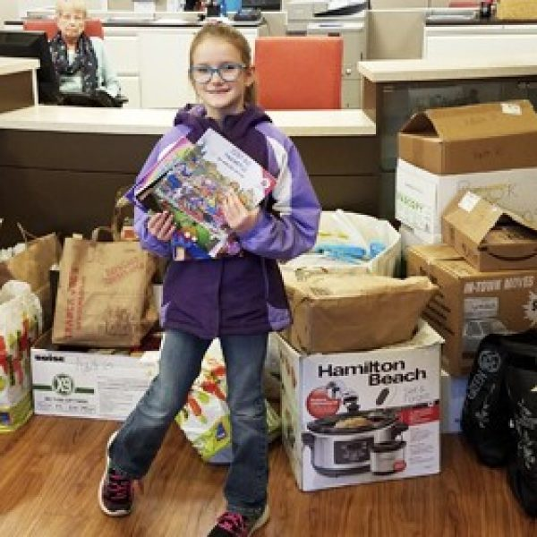 Long Elementary School second-grader Lily Yemm is pictured with the books she collected for the Ronald McDonald House at Mercy Hospital St. Louis.
