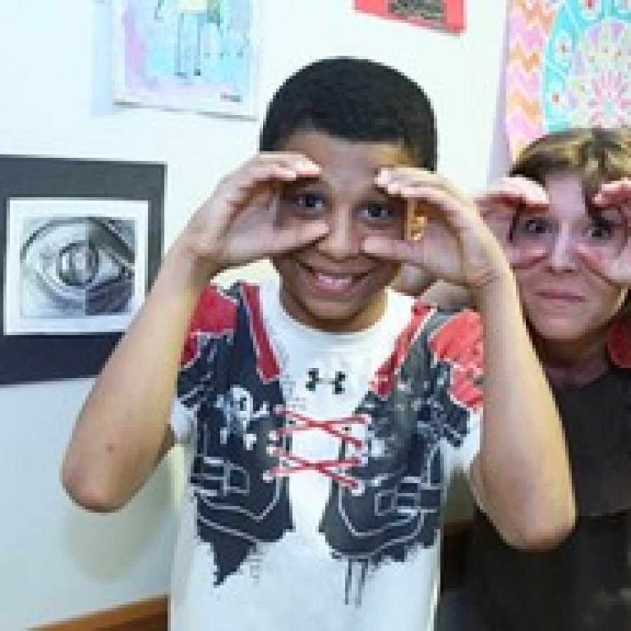 Myles Kee, 11, and art teacher Kris Wollaeger of Kirkwood, mimic Myles art piece at the fifth annual Fountain View Young at Art Show at Friendship Village Sunset Hills. Myles is the son of Lisa Kee of Shrewsbury.