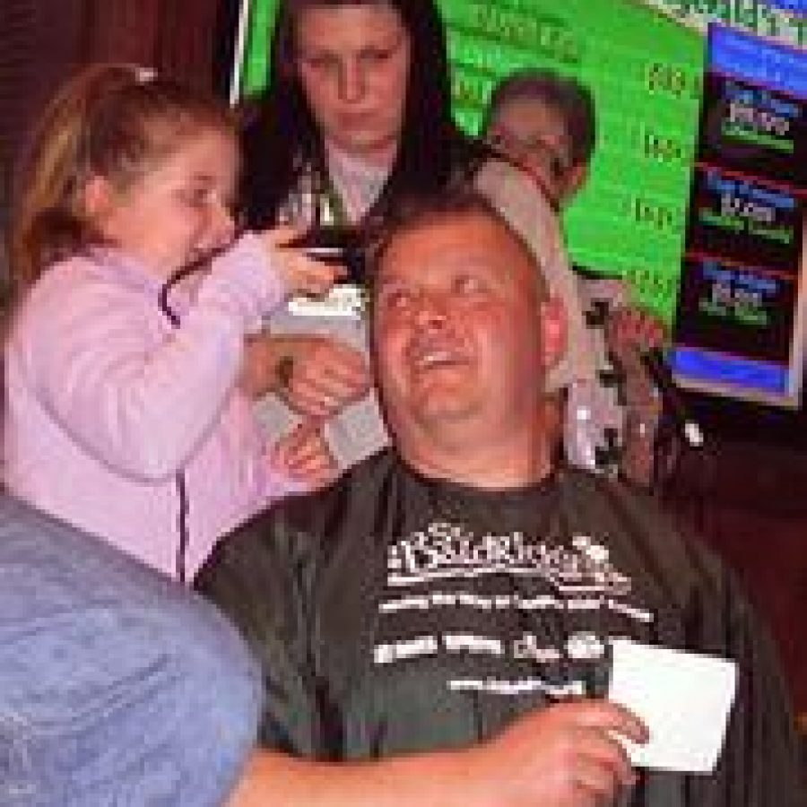 Challia Benae Reed shaves Capt. Kevin Reis' head at the seventh annual St. Baldrick's Foundation Event at Helen Fitzgerald's.