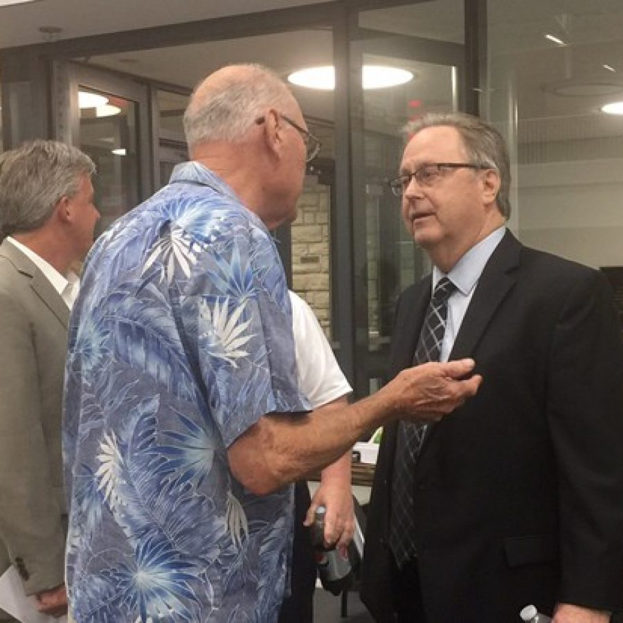 Sixth District County Councilman Kevin O'Leary, D-Oakville, talks to a veteran Tuesday night after a public hearing on selling Sylvan Springs Park to expand Jefferson Barracks National Cemetery. Also pictured in the background is River City Casino General Manager Chris Plant, left.