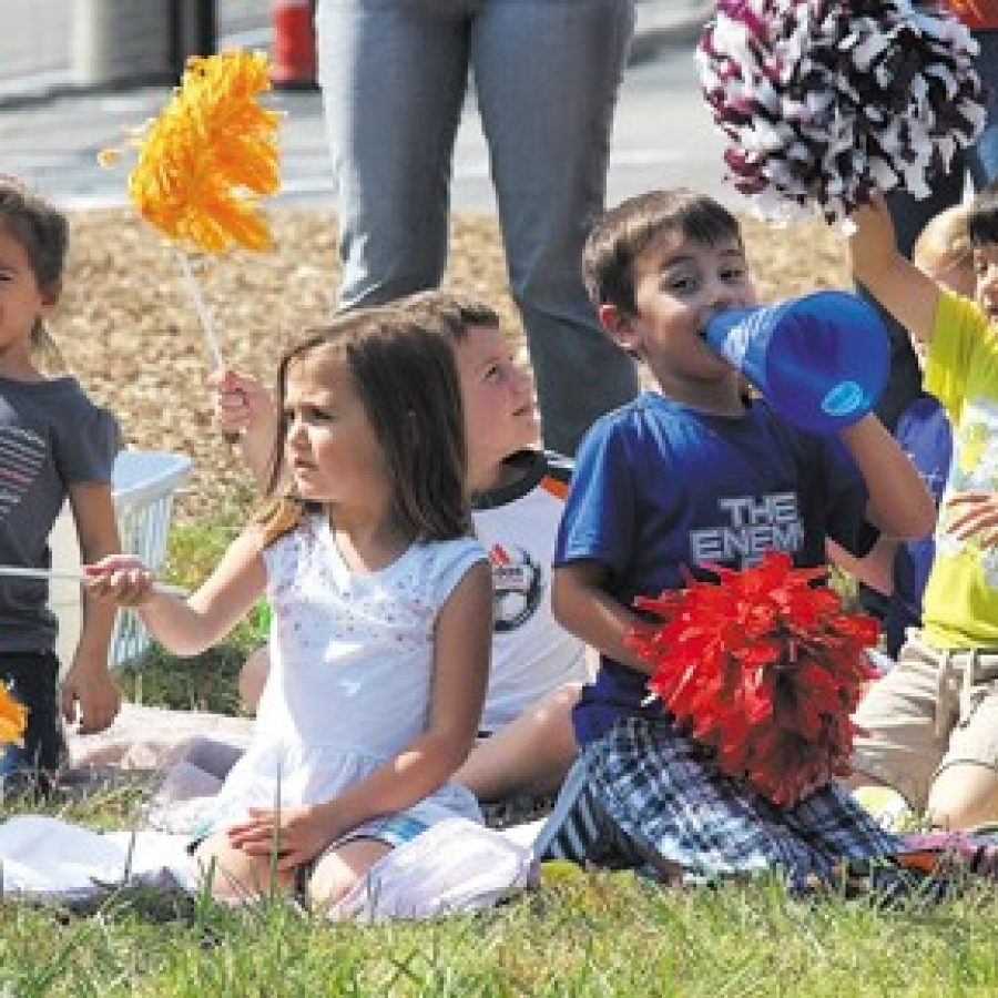 Students in kindergarten through fourth grade line the field to cheer on their older classmates during this year's Character at Play game, while teachers from all grade levels took turns at bat.