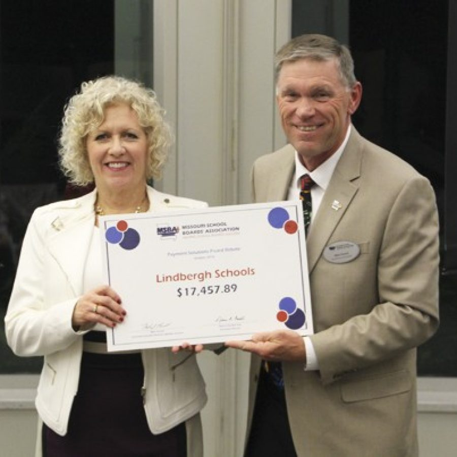 Mike Parnell of the Missouri School Boards' Association presents Lindbergh Board of Education President Kathy Kienstra with a rebate check totaling \$17,457.89 for fiscal 2016.
