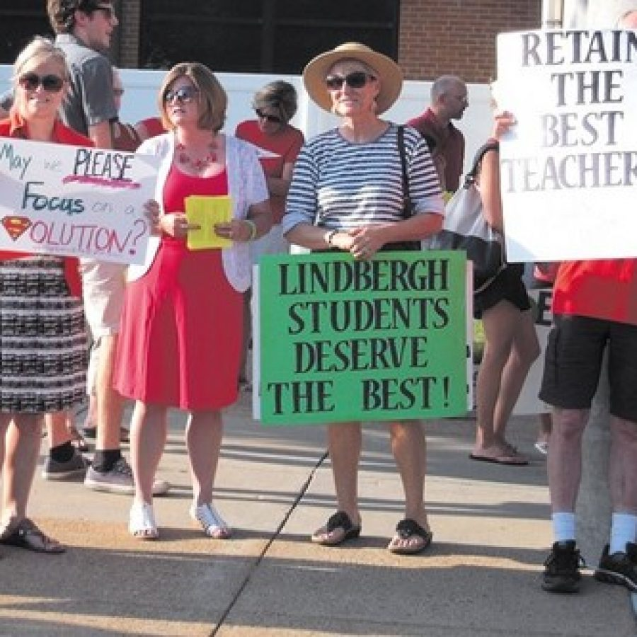 Lindbergh Schools teachers, including Lindbergh National Education Association Vice President Gretchen Moser, second from left, join alumni and residents in front of the Lindbergh High School auditorium before the June 14 Board of Education meeting to express their dissatisfaction with teacher pay. Photo by Mike Anthony.