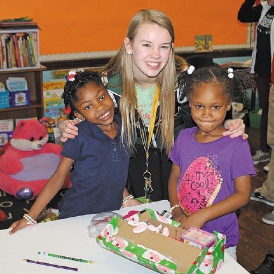 Mehlville High National Honor Society members made their annual trek last week to Clay Elementary School in north St. Louis to continue a holiday tradition. The Shoebox Project provides gifts to nearly 200 Clay students as a way to bring together two distant and different communities. Mehlville High student Logan Merz is pictured with two Clay students.