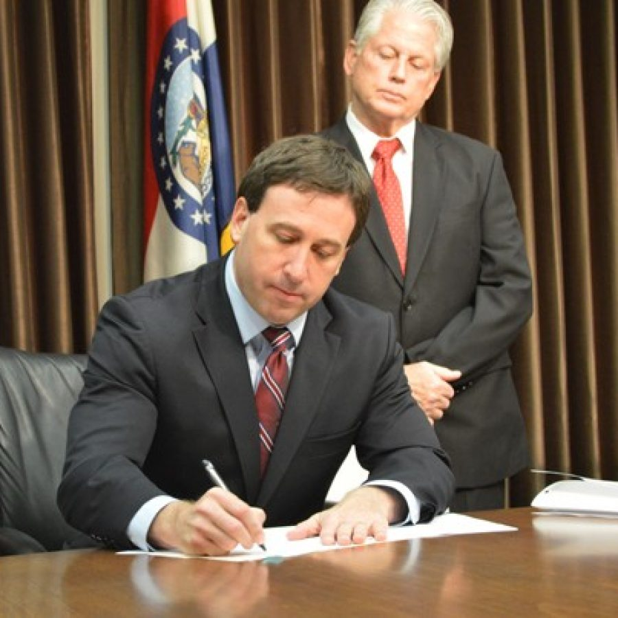 Fifth District Councilman Pat Dolan, D-Richmond Heights, watches as County Executive Steve Stenger signs into law a bill creating the St. Louis County Prescription Drug Monitoring Program.