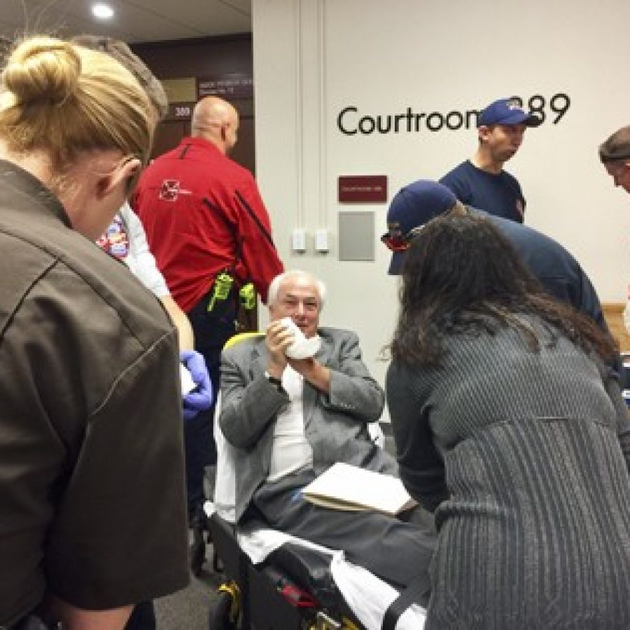 Post-Dispatch reporter Tim O'Neil, sitting, is treated by Clayton paramedics after losing part of a finger Wednesday morning at the St. Louis County Courthouse. Photo by Gloria Lloyd