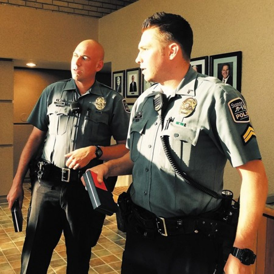 Sunset Hills Police Officer Lee Johnson, left, and Cpl. Jeff Senior speak with residents at City Hall just after receiving their five-year service awards from Police Chief William LaGrand at a recent Board of Aldermen meeting.