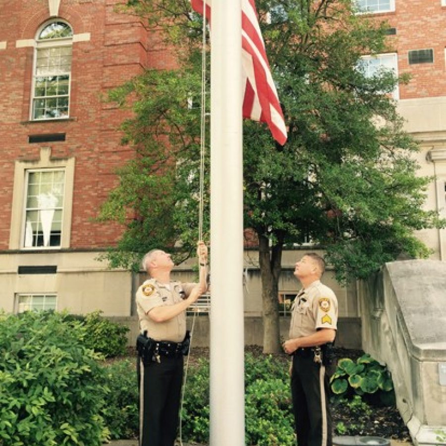 Sgt. Mike Castellano, left, and Sgt. Mike Stoehner lower the flag in front of the St. Louis County Police Department headquarters to half-staff in honor of Officer Blake Snyder, who was killed in the line of duty Thursday morning.