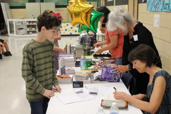Award-winning author Margaret Peterson Haddix signs a book for Truman Middle School seventh-grader Nick Berra.