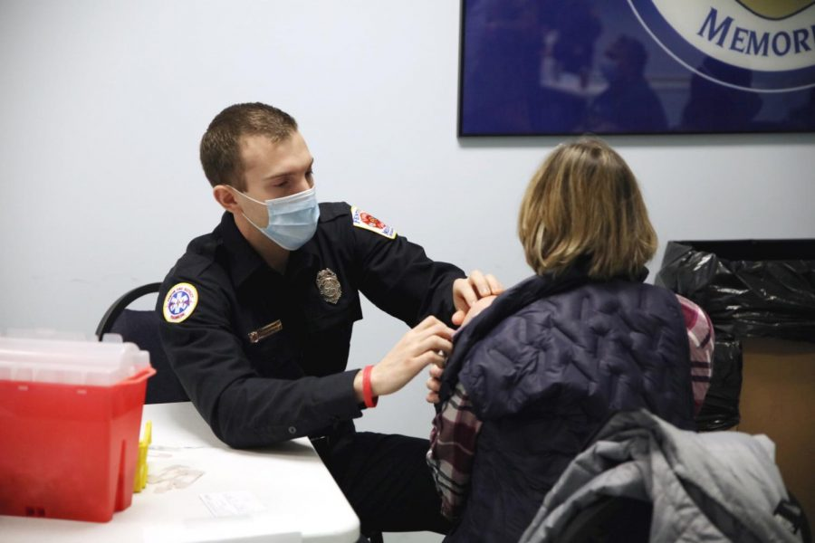A paramedic from the Fenton Fire Protection District, above, gives a COVID-19 vaccine shot to a woman in the community room at the Affton Fire Protection District headquarters on Gravois Road while St. Louis County Executive Sam Page visited Friday. Most of the shots given at the vaccination sites in the Mehlville, Affton and Eureka fire protection districts halted last week, but the fire districts used remaining vaccine doses to vaccinate residents of group homes.