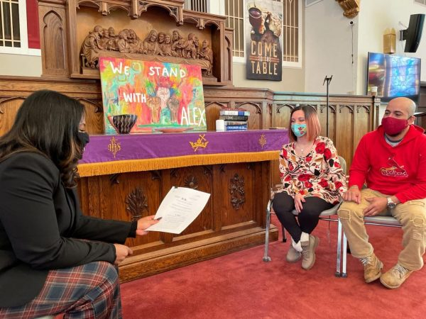 Alex Garcia, right, and his wife, Carly, meet with U.S. Rep. Cori Bush, left, at the church in Maplewood where he lived last week. She gave the Garcias a copy of her private bill to give him permanent residency in the U.S.