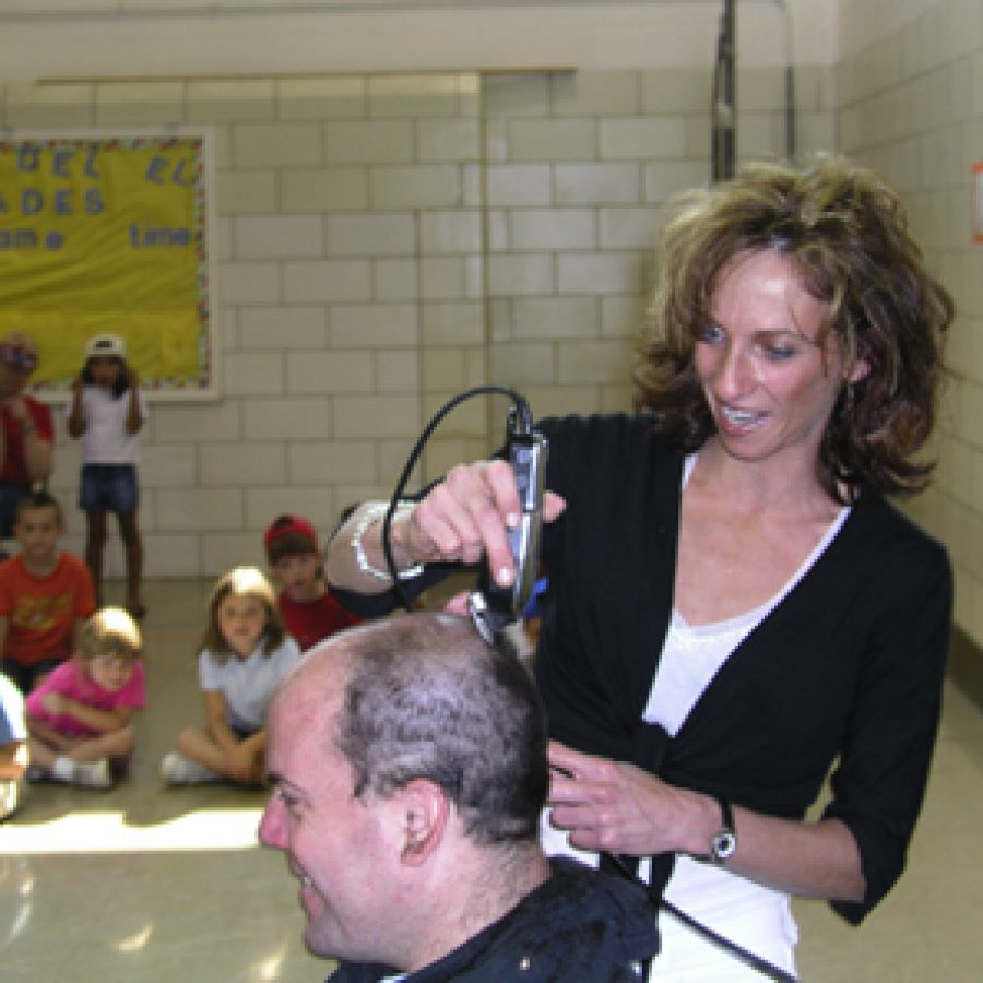 Stylist Shannon Rowan shaves the head of custodian Wayne Auer at Friday's all-school assembly at Blades Elementary School.