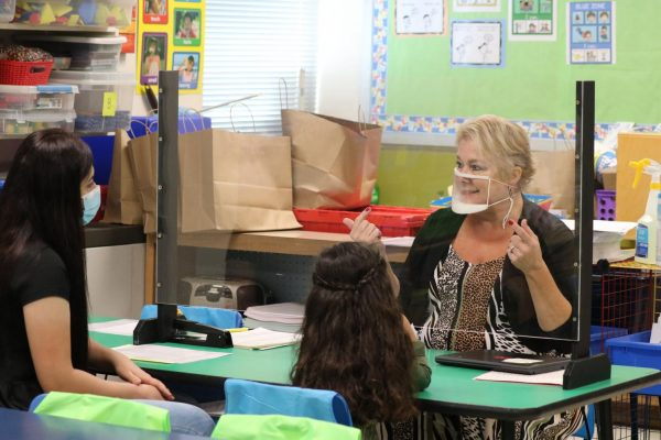 Teacher Samantha Wanko talks to incoming kindergarteners at Bierbaum Elementary  in the Mehlville School District in August about procedures and Chromebook pickup.