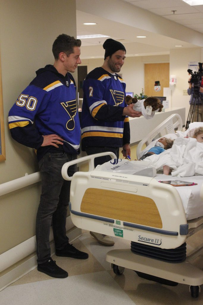 St. Louis Blues players including then-player and Oakville native Patrick Maroon, right, and Jordan Binnington visit with a patient at Cardinal Glennon Children's Hospital around Christmas 2018. Photo by Erin Achenbach.