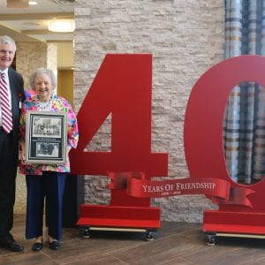 C.E.O. of FV Services, Inc. and Dorris Brown pose in front of the 40 Years of Friendship sign. Brown is holding a photo from her appearance at the first groundbreaking event in 1978. Photo by Jessica Belle Kramer.
