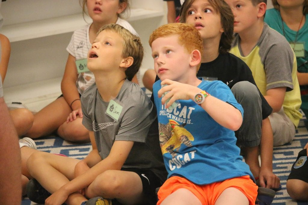 Fourth graders Sam Kappel, left, and Mason Cross listen to Bloxels representative Nick Groninger as he explains how the coding game works in July 2018 before the students play it on their own.